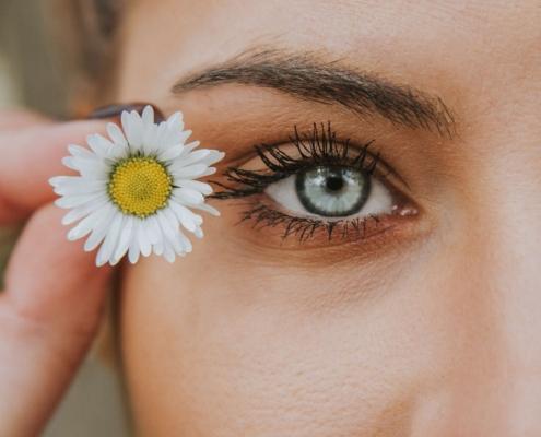 Occhi azzurri, femminile attraente con fiore accanto