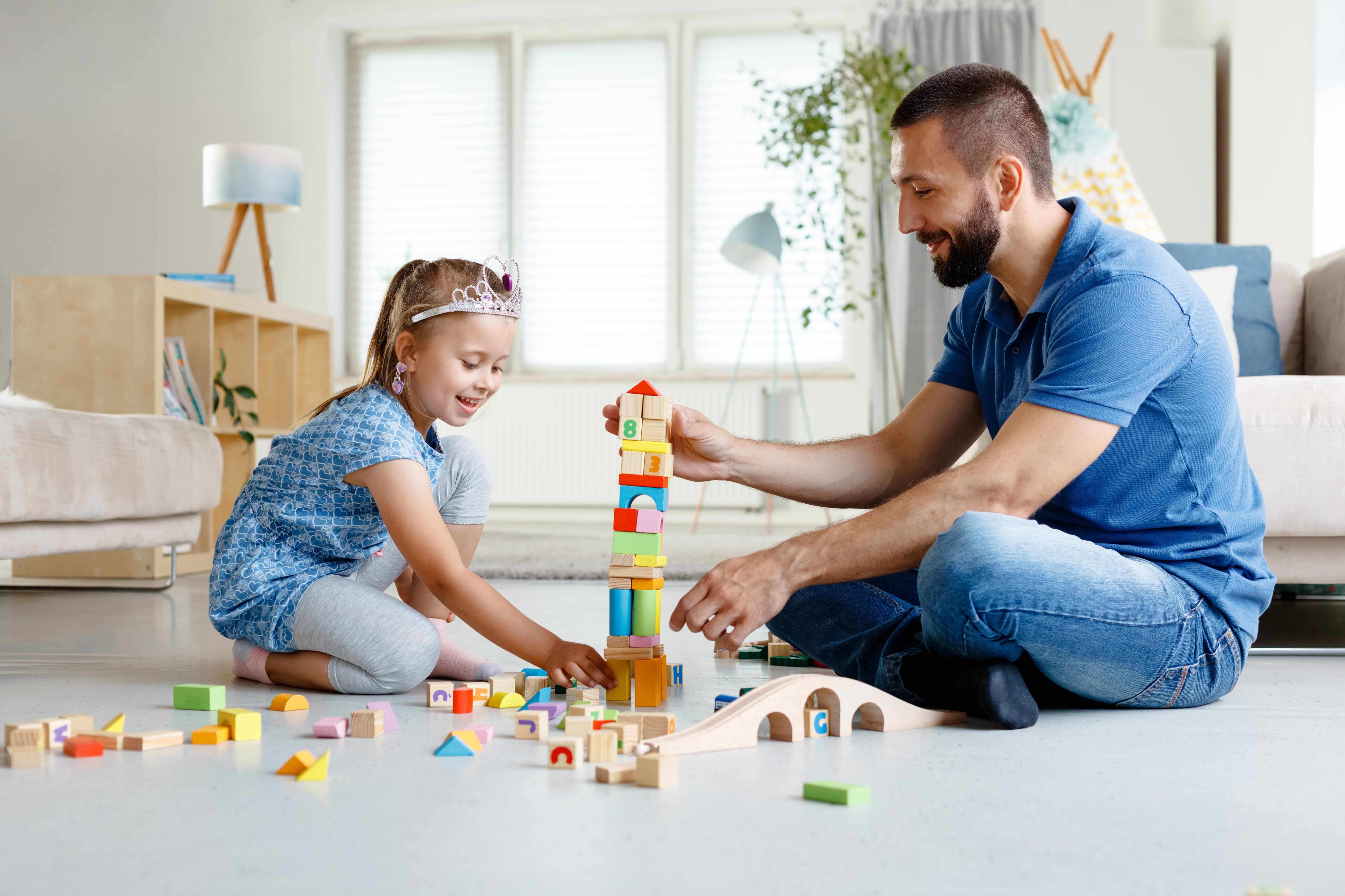 Padre e figlia giocano sereni con le costruzioni